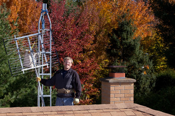 Workman installing HDTV digital antenna on a house