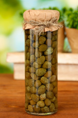 Glass jar with tinned capers on green background