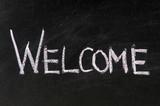 welcome handwritten in script in chalk on a blackboard poster