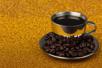 Stainleess stell espresso cup on saucer on golden background