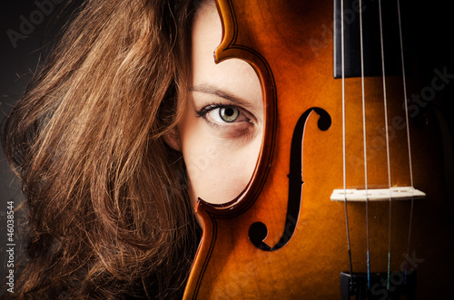 Woman with violin in dark room