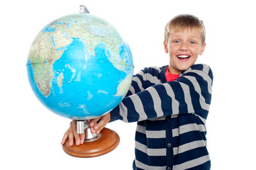 Excited school boy holding globe
