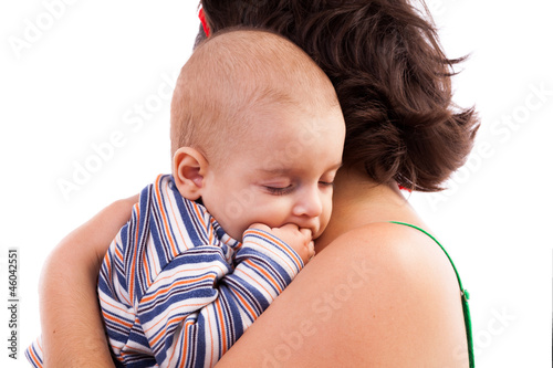 Kid sleeping in his mother's arms