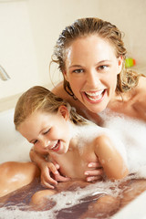 Mother And Daughter Relaxing In Bubble Filled Bath