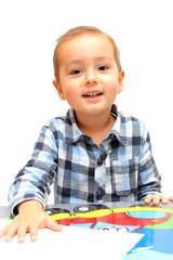 Kind sitzt am Tisch und lächelt