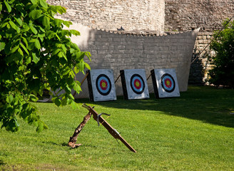 Crossbow and targets in front of limestone wall