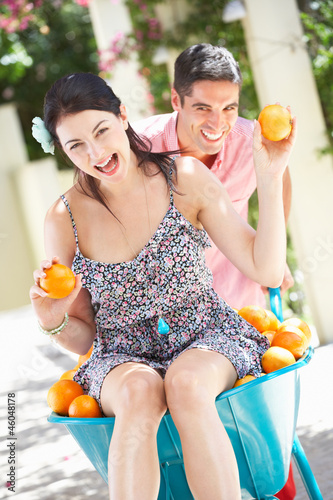 Man Pushing Woman In Wheelbarrow Filled With Oranges