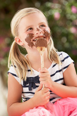 Young Girl Covered In Chocolate Licking Spoon