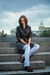 Beautiful young woman sitting on stone steps