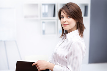 portrait of beautiful young business woman holding folder