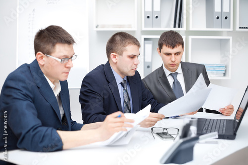 Team of young business men doing some paperwork together
