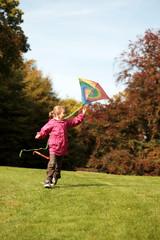 Kleines Mädchen beim Drachen steigen lassen