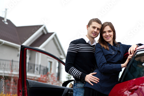young successful family near the car