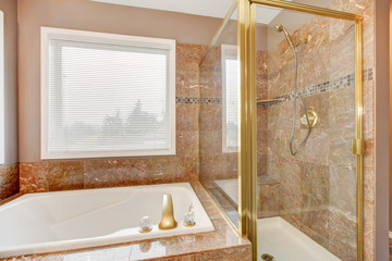 Luxury new granite shower and tub with gold metal.
