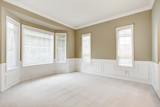 Bright large empty room with carpet, molding and  windows.