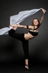 Молодая женщина прыгает с развивающейся тканью.