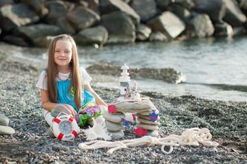 Красивая маленькая девочка на побережье моря.