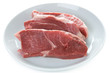 raw lamb leg steaks on a white plate isolated