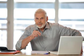 An elderly man using his laptop