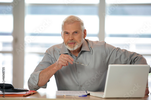 An elderly man using his laptop