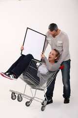 Couple with trolley holding picture frame