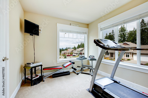 Home gym with equipment, weights and TV.