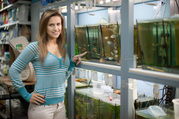 Woman chooses  fish in aquariums
