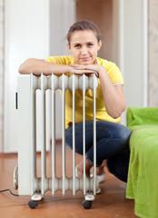 Happy woman near  heater
