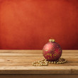 Christmas ornament on wooden table over red grunge background