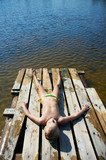 Little girl sunbathing on a raft