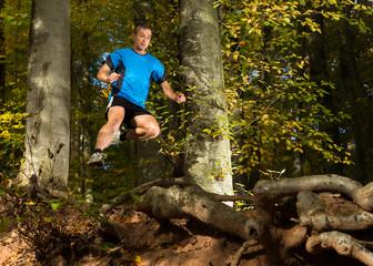 Trailrunner springt über Wurzeln im Wald
