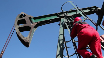 Oil Worker Climbing Pump Jack