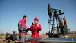 Two Workers in front of Oil Well