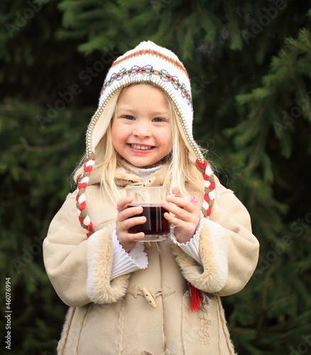 kleines Mädchen mit Kinderpunsch draußen