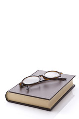 白背景に閉じた本と眼鏡