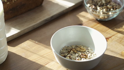 Hand adding walnuts and raisins to muesli in bowl