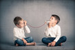 Leinwanddruck Bild - Young brothers talking with tin can telephone