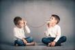 Leinwandbild Motiv Young brothers talking with tin can telephone