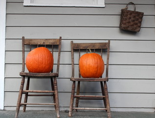 Old wood chairs and bright orange pumpkins