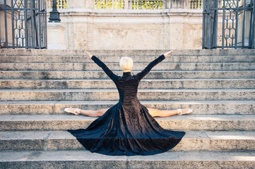 Young beautiful ballerina with black long dress posing on stairs