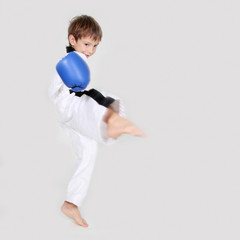 young boy kickboxing fighter in white kimono isolated on white