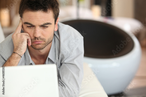 Puzzled man sitting at laptop