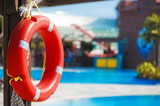 Lifebuoy hanging on a wooden beam at the pool