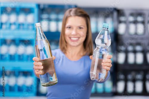 frau zeigt glasflasche und plastikflasche - 46082329