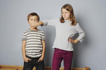 Schwester hält Bruder die Hand vor den Mund
