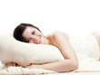 Pretty smiling young woman is lying on her pillow - isolated