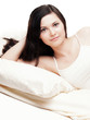Relaxed young leaning on the arm in bed - isolated