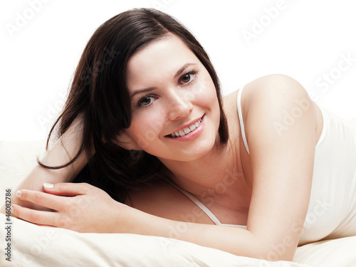 Relaxed young woman smiling in bed - isolated