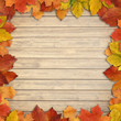 Autumn leaves over wooden