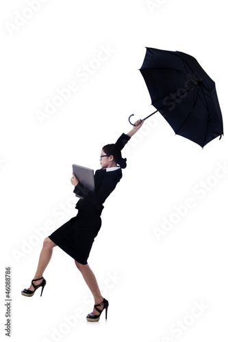 Isolated businesswoman blowing away with umbrella